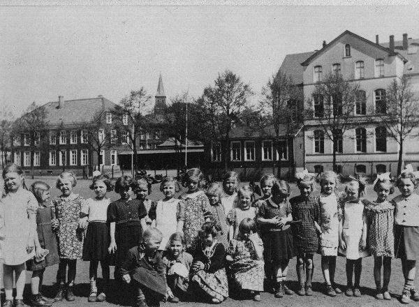 Historisches Klassenfoto - im Hintergrund das Schulgebäude